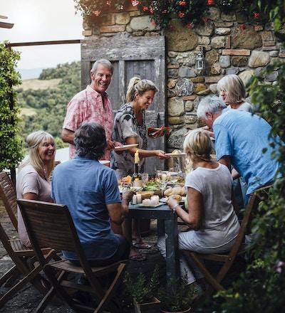 En grupp mogna vänner sitter runt ett matbord utomhus, äta och dricka. De pratar lyckligt och njuter av varandra. Bilden har tagits i Toscana, Italien.