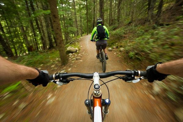 POV-bild av en mountainbiker efter en annan cyklist på en spår