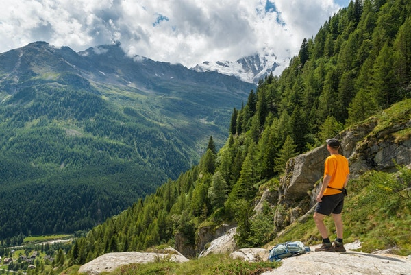 Fotvandrare i bergen på en sommardag. Macugnaga, Anzasca-dalen, Ossola-dalen, Piemonte, Italien. Pittoresk flygfoto över en alpindal med Monte Rosa täckt med is i bakgrunden