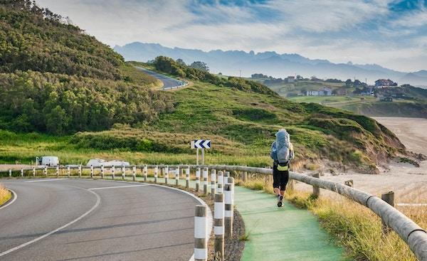 Ensam pilgrim med ryggsäck som går Camino de Santiago i Spanien, väg av St James