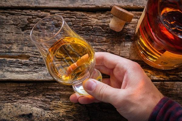 Man som rymmer en lycklig whisky i handen.