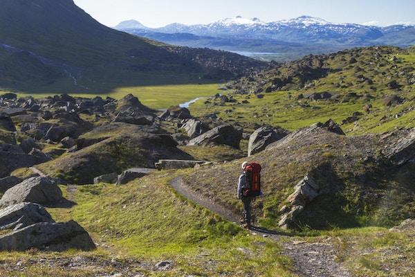 Vita kvinnor, 50-55 år gamla vandrar i fjällområdet i Kiruna svenska lapland i juli månad och det är snö och en glaciär i bakgrunden
