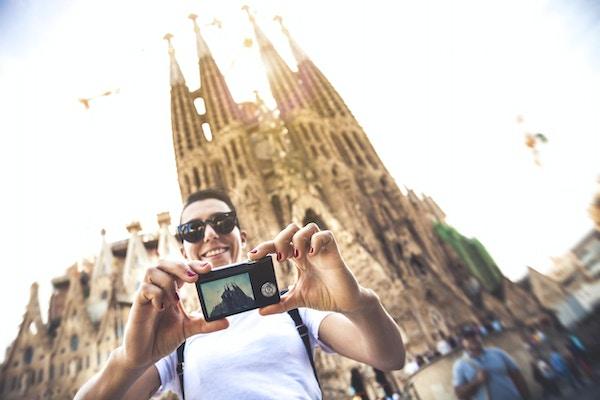 En person som tar en selfie framför Sagrada Familia-kyrkan i Barcelona