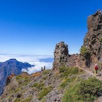 Kvinna som går på vandringsled, från Pico de la Nieve till Roque de los Muchachos, i Caldera de Taburiente nationalpark.