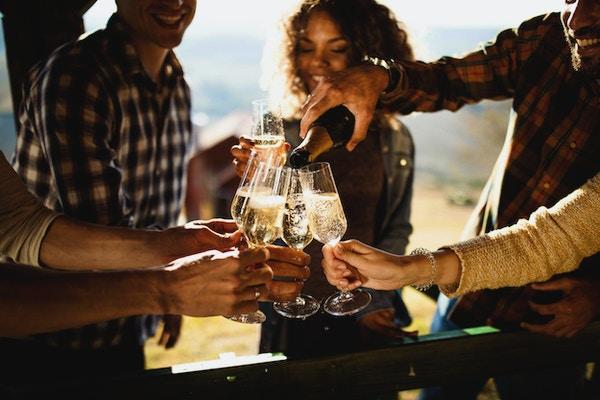 Närbild på lyckliga vänner som har kul medan du dricker champagne på ett terrassparti. En av dem häller.