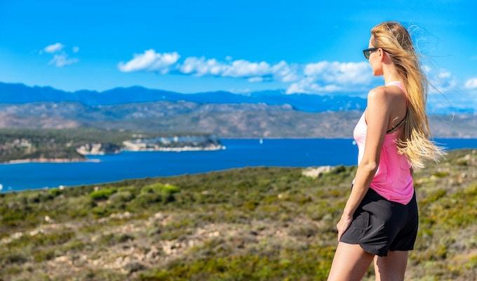 Ung kvinna som tycker om stora semestrar på Korsika. Frihet i vildmarken. Vacker maquis i naturen.