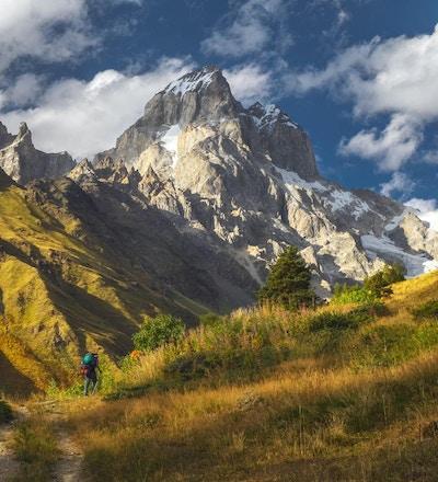 Landskap med berget Ushba i solnedgångljus och turist