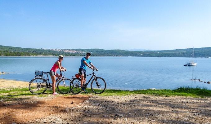 Ett par i sportiga kläder står på sina cyklar vid stranden och beundrar utsikten bakom dem. Kusten är delvis sandig, stenig och gräsbevuxen. Vattnet i viken är lugnt, båt förankrad till stranden