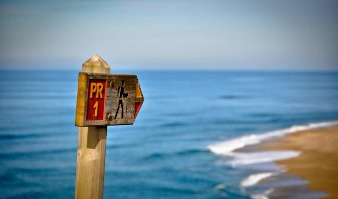 Trail Sign som pekar på stranden.