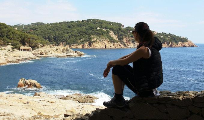 Den unga kvinnan vilar framför Medelhavet under en vårslinga mellan byarna Tamariu och Calella de Palafurgell, Costa Brava, Katalonien, Spanien.