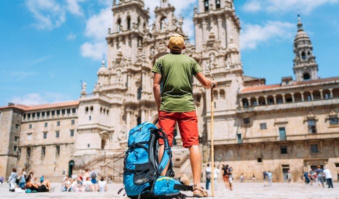 Ung backpackerpilgrim som står på Obradeiro-torget (torget) - huvudtorget i Santiago de Compostela.