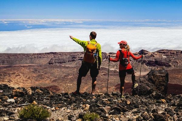 Man- och kvinnafotvandrare som vandrar i sommarberg. Ungt par på en stenig bergkant som ser den härliga sikten.