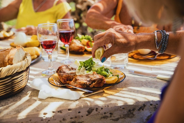 Lady njuter av sin mat serveras med en halv platta kött och den andra halvan sallad. Hon sitter vid bordet med sina vänner i restaurangen på sin semester.