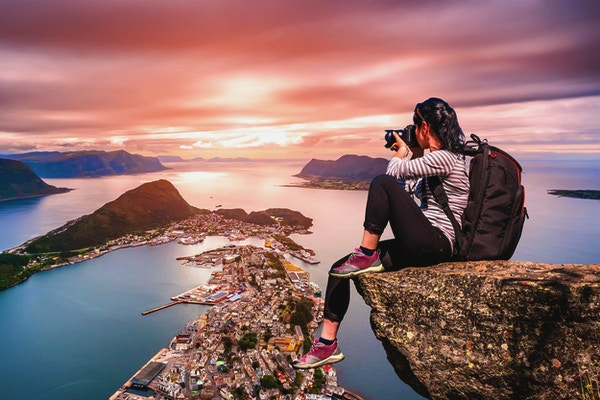 Naturfotograf turist med kameran skjuter medan du står på toppen av berget. Aksla i staden Ålesund, Norge.