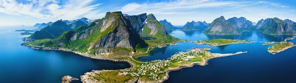 Panoramautsikt över Reine traditionella fiskeläge i Lofoten skärgård i norra Norge med blått hav och berg under solig arktisk sommar