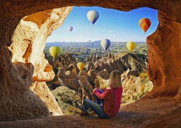 Kvinna som ser färgglada ballonger med varm luft som flyger över dalen på Cappadocia, Turkiet. Vulkaniska berg i Goreme nationalpark.