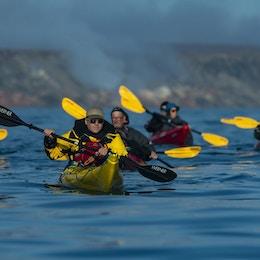 En grupp kajakpaddlare i röda och gula kajaker paddlar ihop utanför Smoking Hills