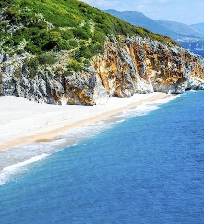 Vit sandstrand, blått hav och stenar. Kan det vara bättre?