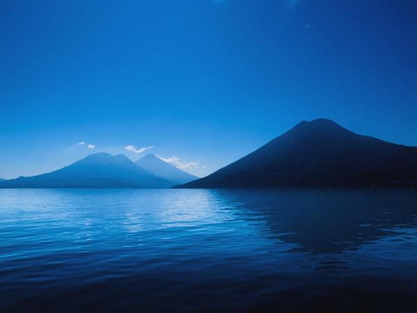 Djupblå: Lake Atitlan, Guatemala silhuett av vulkaner på blå sjö