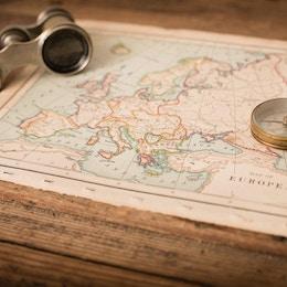 """""""Färgbild av en gammal karta över Europa, från 1800-talet, med kikare och kompass, på träbakgrund. Karta är från en gammal geografibok med 1870 upphovsrätt."""""""