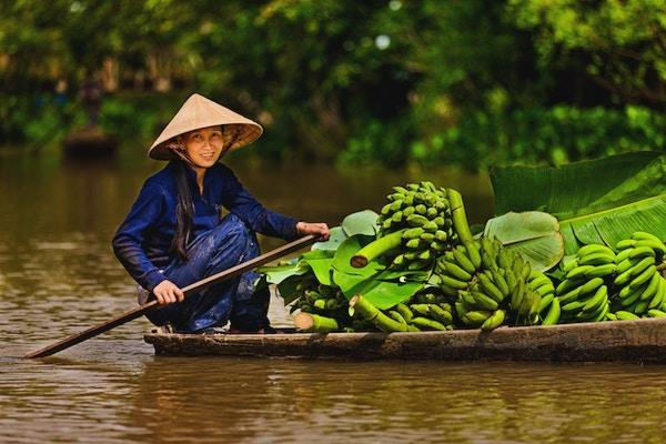 Vietnamesisk kvinna som roar en båt på Mekong River Delta, Vietnam