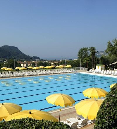 Utomhuspool med solstolar och utsikt över Gardasjön, Poiano Resort, Garda, Italien