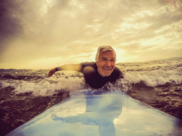 Mycket aktiv äldre man som surfar på en våg med en surfbräda