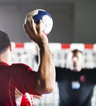 Straffskott. Bakifrån av handbollsspelare som skjuter i mål, medan målvakten är i bakgrunden med upplyfta händer.
