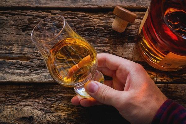 hand håller whisky i ett glas för att smaka på en träbakgrund