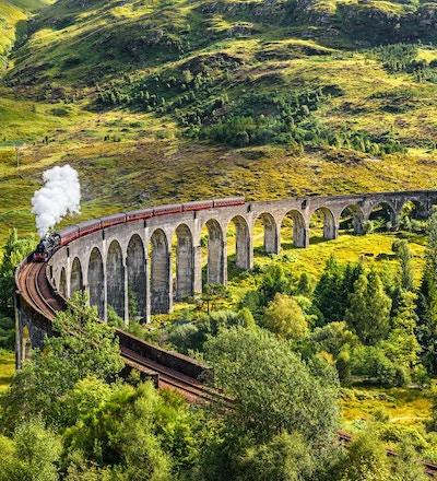 Glenfinnan Railway Viaduct i Skottland med ångtåg passerar.