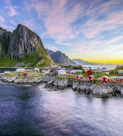 Populär utsikt över fiskehytten (rorbuer) i Hamnoy, Norge med Lilandstinden bergstopp som bakgrund under soluppgång