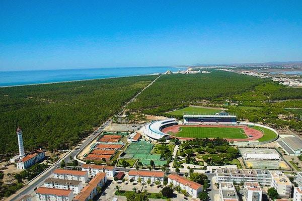 Sportcentret från ovan med kusten och hotellen på stranden i bakgrunden, blå himmel, Atlanten, Monte Gordo, Portugal