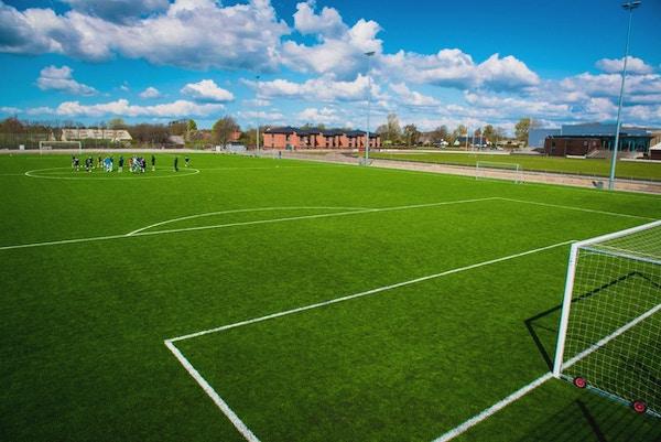 Konstgräsplan, boende i bakgrunden, idrottscenter till höger