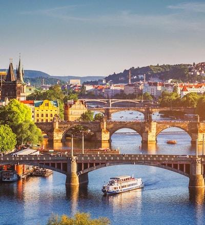 Scenisk vårsolnedgångsikt av den gamla stads pirarkitektur och Charles Bridge över den Vltava floden i Prag, Tjeckien