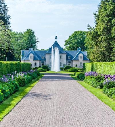 Vacker grusgång omgiven av häckar och blommoar, gångnen leder fram till en sprutande fontän framför Villa Albelin, Norrvikens Trädgårdar, Bjärehalvön, Skåne, Sverige