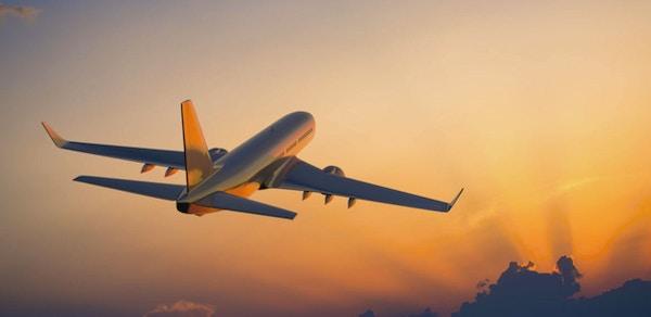Passagerareflygplan som flyger ovanför moln i afton.
