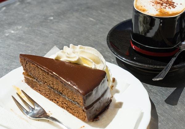 Skiva Sacher Torte eller chokladkaka serverad med färsk grädde och kaffe
