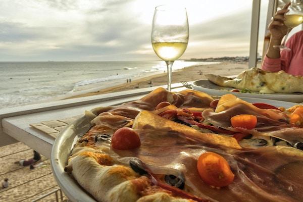 Hemlagad pizza med skinka tomatoliv och paprika med glas vitt vin och stranden vid solnedgången i bakgrund