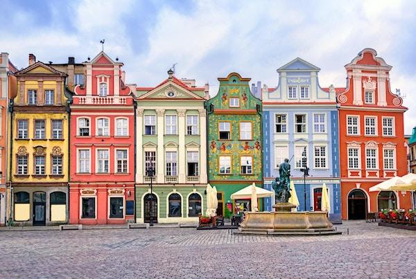Torget med kullerstensgata, fontän och färgglada hus