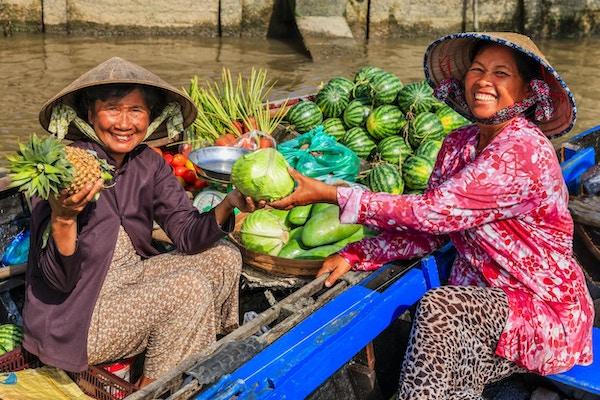 Vietnamesisk kvinna som säljer frukter på den flytande marknaden, Mekong River Delta, Vietnam