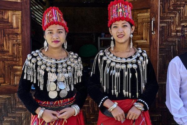 Två lokala damer i traditionella dräkter med silver och röda färger. Foto.