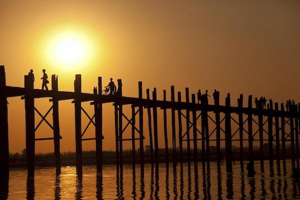 U Bein Bridge vid solnedgången med människor som korsar Ayeyarwady River, Mandalay, Myanmar