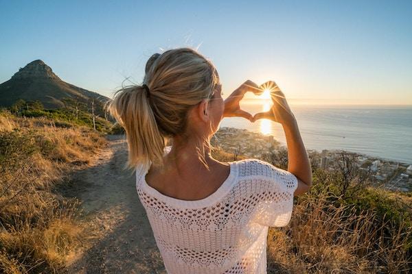 Ung kvinna vid havet som tittar på solnedgången och gör fingraramen för hjärtaform. Skott i Kapstaden, Sydafrika.