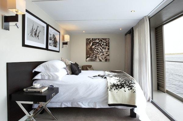 Stuga med dubbelsäng, sängbord, filtar, kuddar, bilder på väggarna och stort fönster. Foto.
