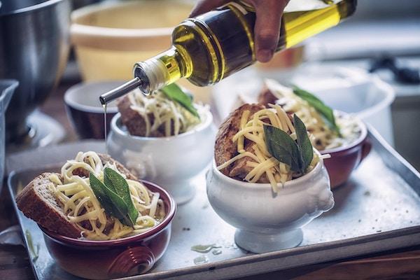 Förbereder fransk lök soppa med läckra långsamt kokta lökar, rostat bröd, ost och färsk salvia