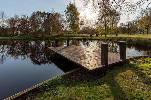 Damm, brygga, träd, grönområden, blå himmerl, solig vårmorgon, Brunnsparken, Ronneby, Sverige