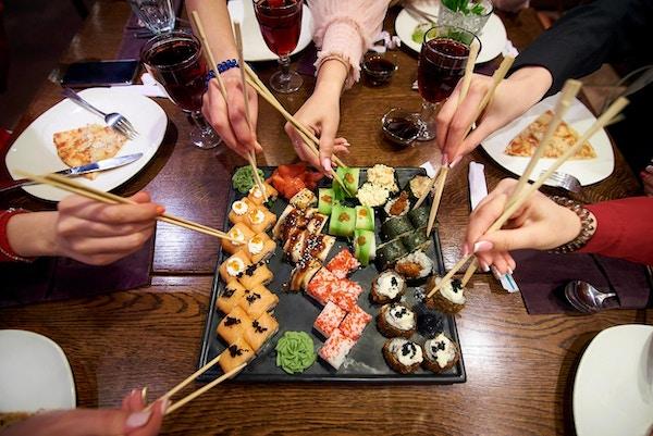 En uppsättning av sushirullar på en tabell i en restaurang. Ett parti vänner som äter sushirullar med bambupinnar.