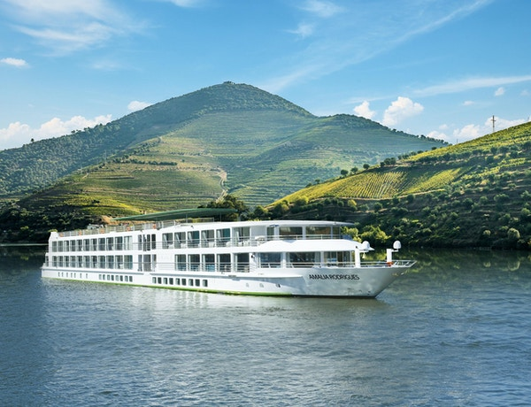 Fartyg som seglar på Douroel-floden längs gröna vinstockar. Foto.