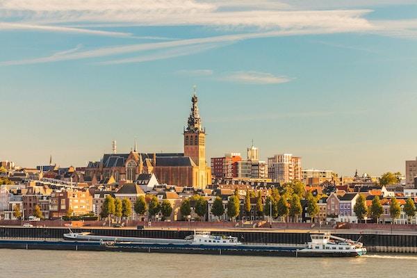 Den holländska staden Nijmegen under solnedgång med floden Waal framme