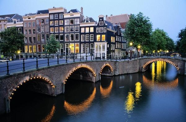 Bro över kanalen i skymningen, Amsterdam, Nederländerna